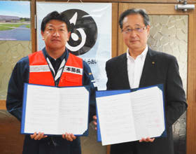 協定書を交換する戸田町長と片岡工場長(右)
