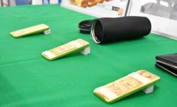 キム被告らが宮崎空港に密輸しようとした金塊3キロと、金塊が隠されていた水筒=宮崎南署