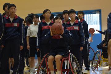 車いすバスケットボールのシュートに挑戦する生徒=坂東市猫実