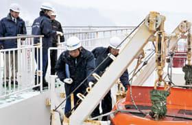 フェリー備え付けの緊急用ボートの管理状況を確認する海保職員