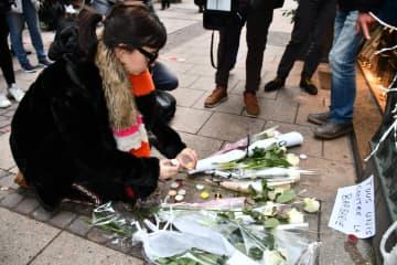 銃乱射事件の犠牲者を追悼し、花をささげてろうそくに火をともす女性=12日、フランス東部ストラスブール(共同)