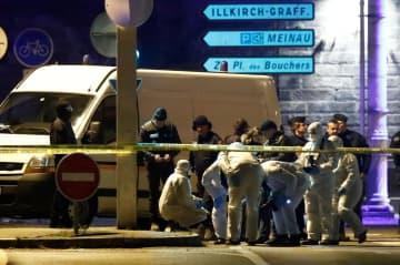 13日、銃撃テロ容疑者が射殺されたフランス東部ストラスブールの路上で、任務に当たる捜査官(ロイター=共同)