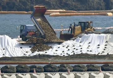 米軍普天間飛行場の移設先、沖縄県名護市辺野古の沿岸部で始まった埋め立て用土砂の投入作業=14日午前11時2分