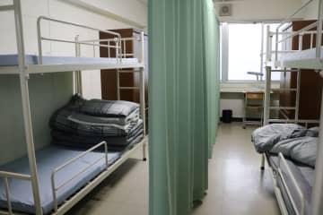 カーテンで仕切られた受刑者の部屋=21日午後、愛媛県今治市