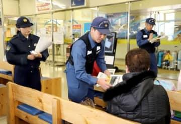 漂着船について注意を呼び掛けるチラシを配る9管職員ら=21日、新潟市中央区の佐渡汽船新潟港ターミナル