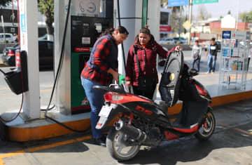 メキシコ市郊外のガソリンスタンドでスクーターに給油する従業員=11日(ロイター=共同)