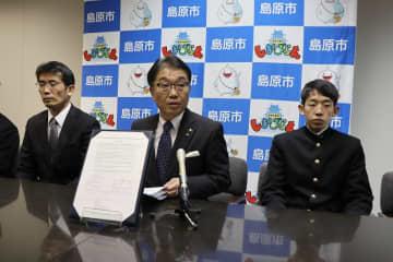 事前キャンプ実施の合意について記者会見する古川市長(中央)=島原市役所外港庁舎
