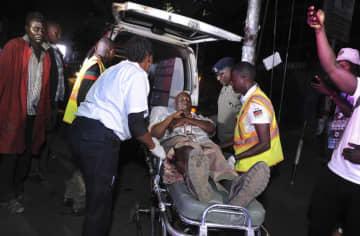 26日、ナイロビの爆発現場から搬送される負傷者の男性(AP=共同)