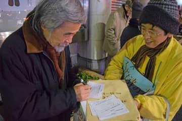 街頭で投票を呼び掛ける実行委メンバー(右)=京都市下京区