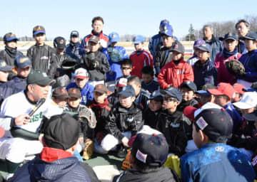 専大北上高の中尾孝義監督(左)からキャッチングの技術指導を受ける児童ら