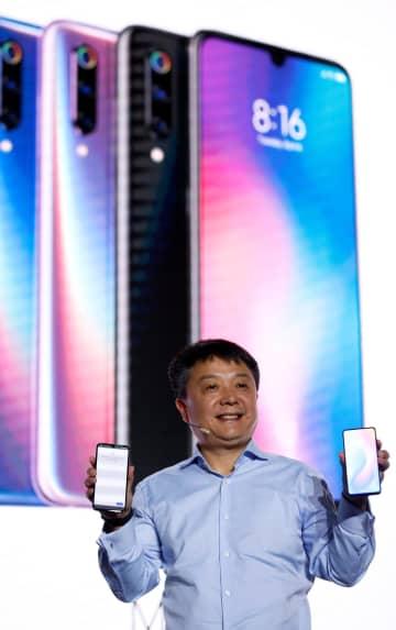 新型スマートフォン「Mi 9」を披露するシャオミ幹部=24日、スペイン・バルセロナ(ロイター=共同)