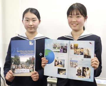 「高校生平和大使」の歩みを振り返る写真集を手にする中村涼香さん(右)と山口雪乃さん=1日午後、長崎市
