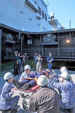護衛艦ひゅうがの甲板からエレベーターで救助者を船内に運ぶ海上自衛隊の隊員たち(京都府舞鶴市北吸・海自北吸桟橋)