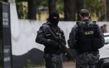 乱射事件が発生した学校の前で警戒する警察官=13日、ブラジル・サンパウロ郊外(ロイター=共同)
