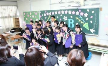 教室でクラスメートや担任教諭と記念写真を撮る卒業生