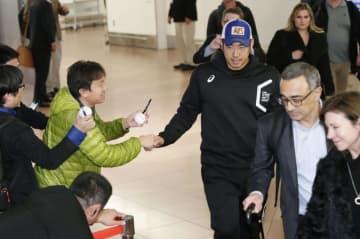 米大リーグ、マリナーズの開幕戦に臨むため羽田空港に到着し、ファンに握手を求められる菊池雄星投手(中央)=15日午後