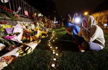ニュージーランド・クライストチャーチの銃乱射事件で、市が設けた追悼場所を訪れ犠牲者を悼む子どもたち=16日(共同)