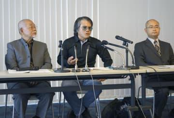 那覇地裁での判決後、記者会見する芥川賞作家の目取真俊さん(中央)=19日午前、那覇市