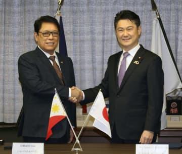 協力覚書に署名し、握手する山下法相(右)とフィリピンのシルベストレ・ベリヨ労働雇用相=19日午後、法務省