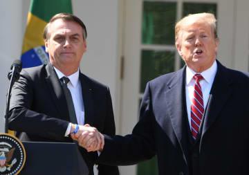 19日、米首都ワシントンでトランプ大統領(右)と握手するブラジルのボルソナロ大統領(UPI=共同)