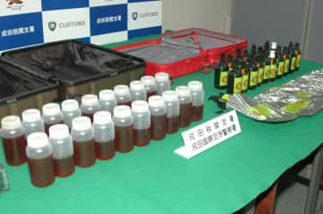 押収された「t-BOCメタンフェタミン」の液体(手前)と隠されていたマッサージオイルの瓶など=20日、成田空港第2ターミナル