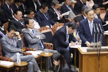 参院予算委で答弁する菅官房長官。左端は安倍首相=27日午前