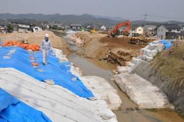 本復旧工事が進む末政川の堤防決壊箇所=倉敷市真備町有井