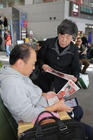 韓国便の乗客にチラシを手渡す中村クニさん=6日、新潟空港