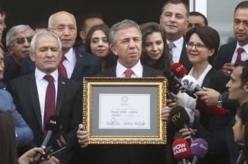 トルコ・アンカラで、市長選の当選証書を受け取った後に記者団に話すヤワシュ氏(中央)=8日(アナトリア通信提供・共同)