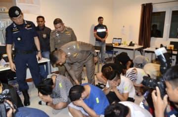 タイ中部パタヤの振り込め詐欺グループの拠点で、調べを進める当局者(中央)と逮捕された容疑者ら=3月30日