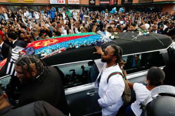 米人気男性ラッパー、ニプシー・ハッスルさんの遺体を載せた車を見守る人々=11日、ロサンゼルス(ロイター=共同)