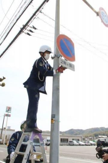 事故現場付近の道路標識を点検する玉島署員=倉敷市玉島勇崎