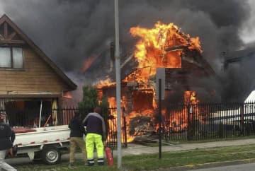 小型機が墜落し、炎上した住宅=16日、チリ・プエルトモント(ロイター=共同)