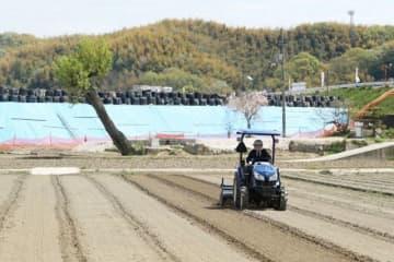 西日本豪雨で被害に遭った田んぼをトラクターで掘り起こす小野さん。決壊した高馬川の堤防を覆うブルーシートと土のうを背に、米作りを再出発させた=倉敷市真備町箭田