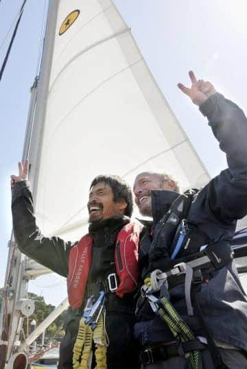 米国西海岸から小型ヨットで太平洋を横断し、小名浜港に到着した岩本光弘さん。右は同乗した米国人男性=20日午前9時すぎ、福島県いわき市