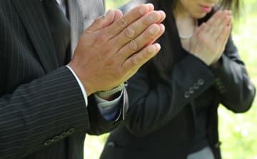 男子生徒が亡くなった現場で手を合わせる両親=長崎県長崎市本河内1丁目