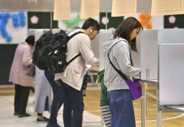 統一地方選の投票用紙に記入する有権者=21日午前、東京都中央区