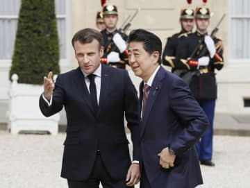 フランスのマクロン大統領(左)の出迎えを受け、共同記者発表に臨む安倍首相=23日、パリの大統領府(共同)