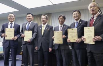 10日、石田総務相(中央左)から5Gの基地局開設の認定書を交付された携帯大手の社長ら=東京都千代田区