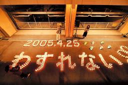 祈りの杜で鎮魂のキャンドルを並べ犠牲者を悼む=24日夜、尼崎市久々知3(代表撮影)