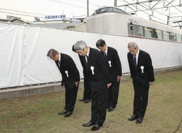 事故発生時刻に合わせ、電車がぶつかったマンションの前で黙とうするJR西日本の来島達夫社長(手前)ら=25日午前9時18分、兵庫県尼崎市(代表撮影)