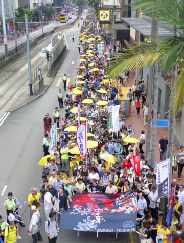 「逃亡犯条例」改正に反対し、デモ行進する民主派=28日、香港(共同)
