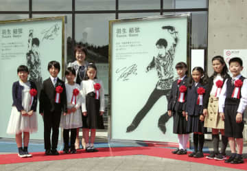 新たに設置された羽生結弦選手のモニュメント(右側)の前で、記念写真に納まる子どもたち。左列後ろは郡和子・仙台市長=29日午後、仙台市の地下鉄東西線国際センター駅