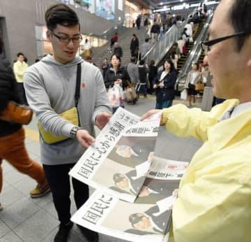 前天皇陛下の退位を報じる号外を手にする人たち=30日午後7時8分、JR岡山駅