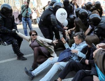 1日、ロシア北西部サンクトペテルブルクで、デモ行進の参加者らを拘束する警察官(ロイター=共同)