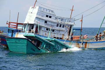 沈没処理されるベトナム漁船(手前)=4日、インドネシア・カリマンタン島西方沖(同国海洋・水産省提供・共同)