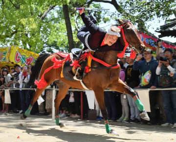疾走する馬の上で大技を披露する乗子の男性(京都市伏見区・藤森神社)