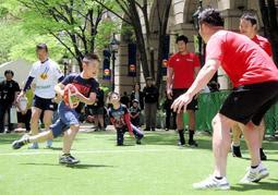 人工芝の上で元気いっぱいのプレーを見せる子どもたち=神戸市中央区明石町