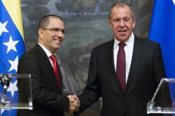 5日、共同記者会見後に握手を交わすロシアのラブロフ外相(右)とベネズエラのアレアサ外相=モスクワ(AP=共同)
