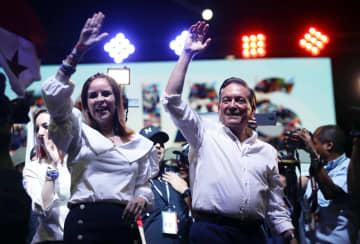 5日、パナマの大統領選で勝利を決め、手を振る民主革命党(PRD)のコルティソ氏(右)とジャスミン夫人=パナマ市(ロイター=共同)